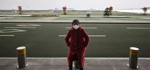 Une passagère attend à l'extérieur de l'aéroport de Tianhe, à Wuhan, le 11 avril 2020. Hector RETAMAL / AFP