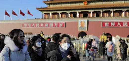 Des gens portent des masques près de la tour de la porte de Tiananmen à Pékin, en Chine © EPA/WU HONG