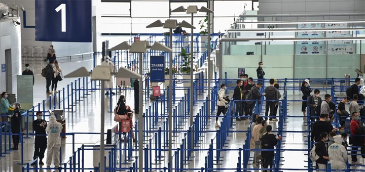 Passengers wearing face masks observe distancing guidelines at Shanghai Pudong International Airport on March 18. © AFP