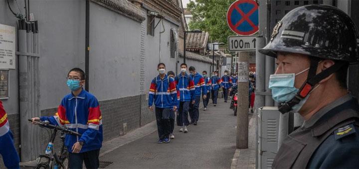 Des élèves portant des masques passent devant un agent de sécurité à leur sortie du collège, à Pékin, en Chine, le 11 mai 2020. © ROMAN PILIPEY / EPA