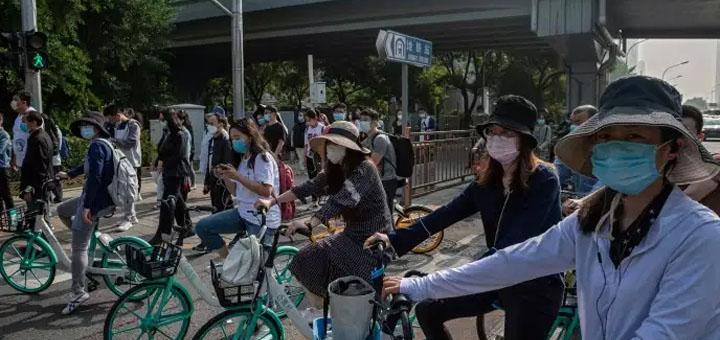 Des hordes de cyclistes masqués à Pékin, vendredi 22 mai. © NICOLAS ASFOURI / AFP.