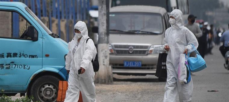 Deux femmes portent des combinaisons de protection lorsqu'elles marchent dans une rue près du marché fermé de Xinfadi à Pékin le 13 juin. © GREG BAKER / AFP
