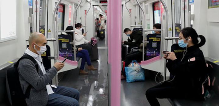 Des passagers portant des écouteurs utilisent leur téléphone portable lors d'un trajet en métro à Wuhan, capitale de la province du Hubei (centre de la Chine), le 29 mars. © Wang Jing / China Daily