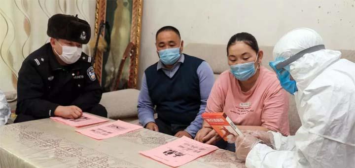 Des policiers chinois en visite chez des résidents de la ville d'Altay dans la région autonome du Xinjiang, le 19 février 2020. STR / AFP