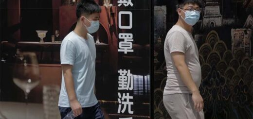"""People pass a restaurant in Beijing displaying an ad saying """"wear a mask and wash hands"""". The Lancet has praised aspects of China's response to the pandemic, including widespread use of masks. © AP"""