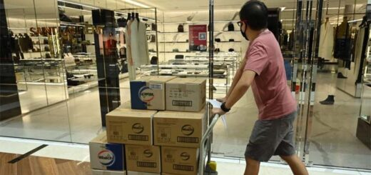 A worker pushes a trolley with goods past a luxury outlet at Marina Bay Sands shopping centre in Singapore. © AFP