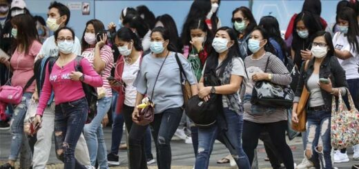Pedestrians and foreign domestic helpers wearing face masks cross a road in Hong Kong's Central district. © Nora Tam