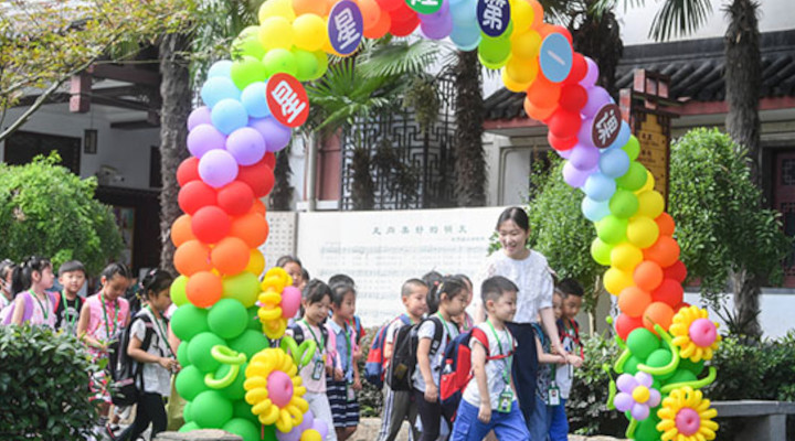 Des élèves qui retournent en classe sont accueillis le 27 août par un enseignant de l'école primaire de Fuzimiao, à Nanjing, dans la province du Jiangsu (est de la Chine). © Shao Dan / China Daily