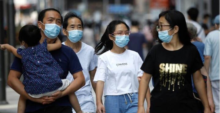 Ce vendredi 21 août dans une zone commerciale de Pékin. Le masque n'est plus obligatoire en extérieur, mais les habitants continuent de le porter. © Reuters / Tingshu Wang
