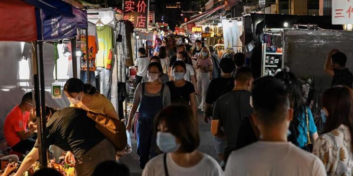 Des habitants sur un marché de nuit à Wuhan (Chine), le 6 août 2020. © AFP/Hector Retamal
