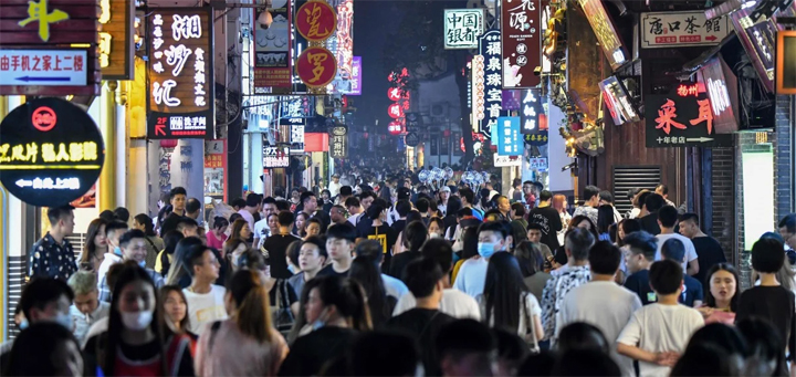 "People walk along a pedestrian street surrounded by small shops in Changsha in China's Hunan province. Coronavirus-ravaged economies across the Asia-Pacific will make a ""swoosh-shaped"" recovery next year, the Asian Development Bank forecast. © AFP"