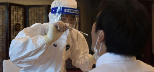 A worker in a protective suit takes a swab to test for Covid-19. © AFP