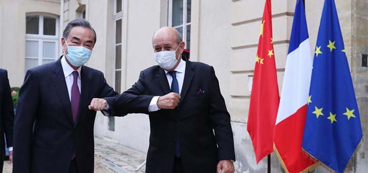 Visiting Chinese State Councilor and Foreign Minister Wang Yi (L) touches elbows with French Foreign Minister Jean-Yves Le Drian in Paris, France, Aug. 29, 2020. © Xinhua/Gao Jing