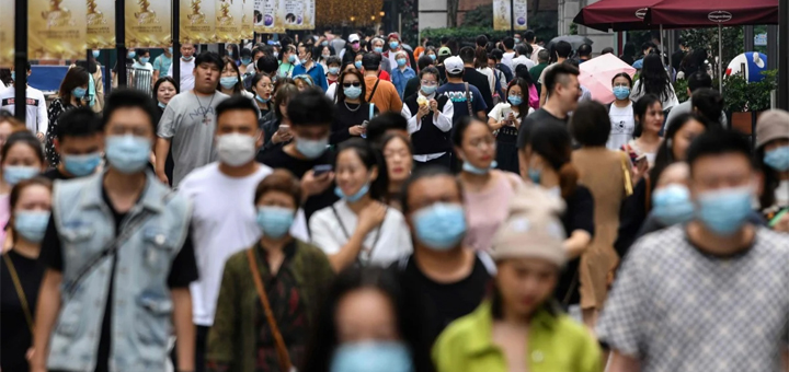 People in Wuhan are out and about wearing masks on September 27, 2020. A new study by Chinese data scientists say in the early days of the outbreak in Wuhan, the virus reproduction number was 7.9. © AFP