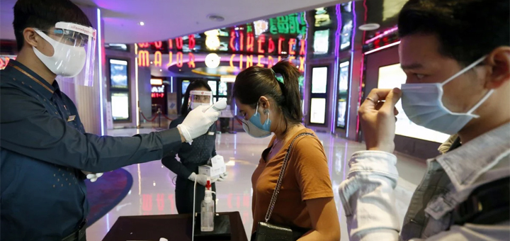 Cinema patrons get their body temperature checked as part of Covid-19 screening. Design changes to entertainment premises are needed in the long run to fight the virus. © EPA-EFE