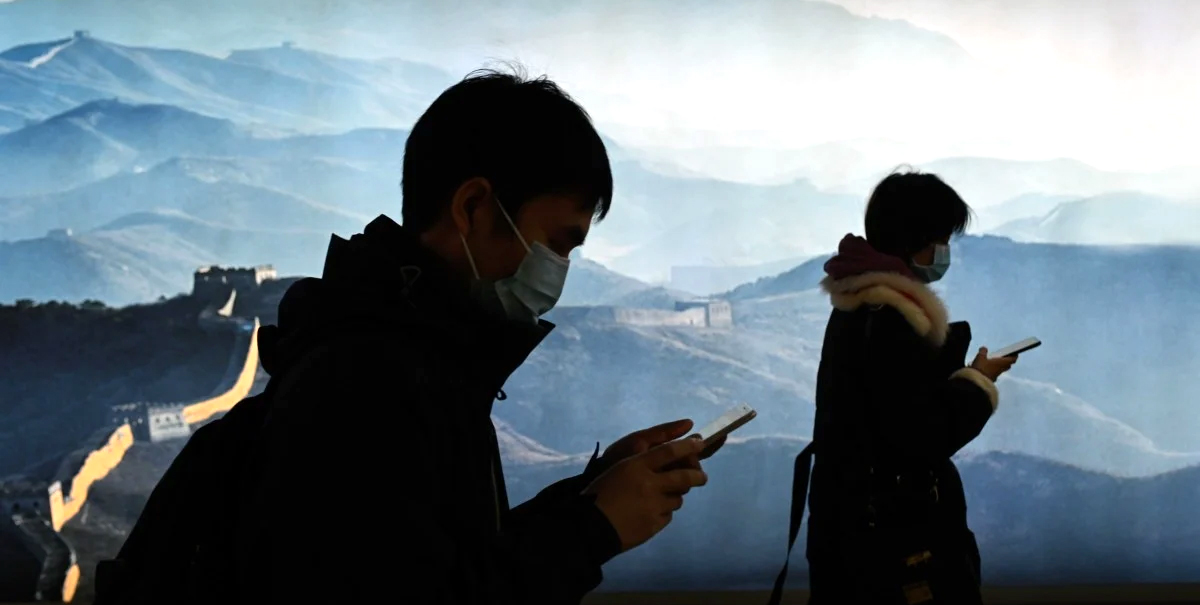 A man and a woman wearing face masks use their mobile phone as they walk in a subway station in Beijing on March 11. © AFP