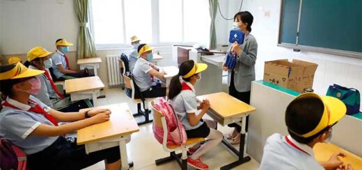 A teacher distributes epidemic prevention materials for students at Fengtai No 1 Primary School in Beijing © China News Service/Getty Images