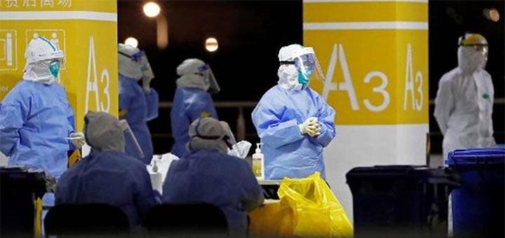 Du personnel médical en combinaison de protection intégrale teste le personnel de l'aéroport de Pudong, à Shanghai (Chine). © AFP