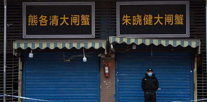 A security guard stands outside the Huanan Seafood Wholesale Market in Wuhan where the coronavirus was detected in January. No date has been announced for the WHO team to go to Wuhan. © AFP