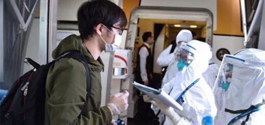 Des agents des douanes demandent et enregistrent les informations de passagers entrants à l'aéroport international de Beijing, le 18 mars 2020. © Xinhua
