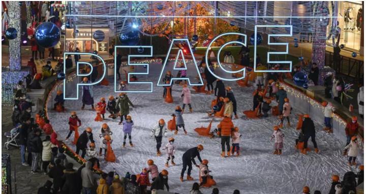Dans ce centre commercial de Pékin, les familles profitent de la patinoire et du marché de Noël, le 20 décembre. © KEVIN FRAYER/Getty Images/AFP