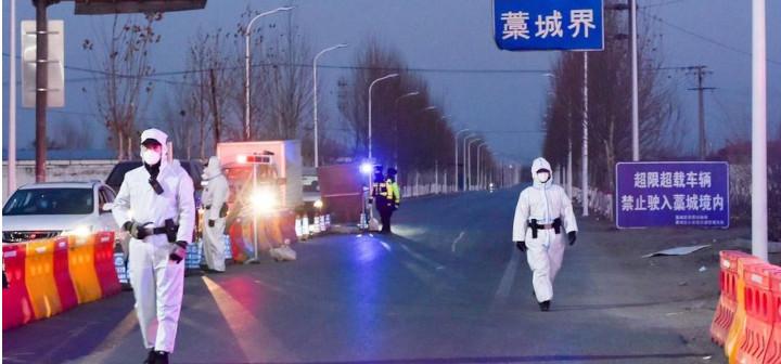 Des policiers en combinaison contrôlent les véhicules à l'entrée du district de Gaocheng, dans la province du Hebei, le mardi 5 janvier. © REUTERS/China Daily