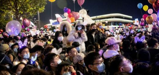 Des habitants masqués de Wuhan attendent le décompte du Nouvel an, le 31 décembre 2020 © NOEL CELIS / AFP