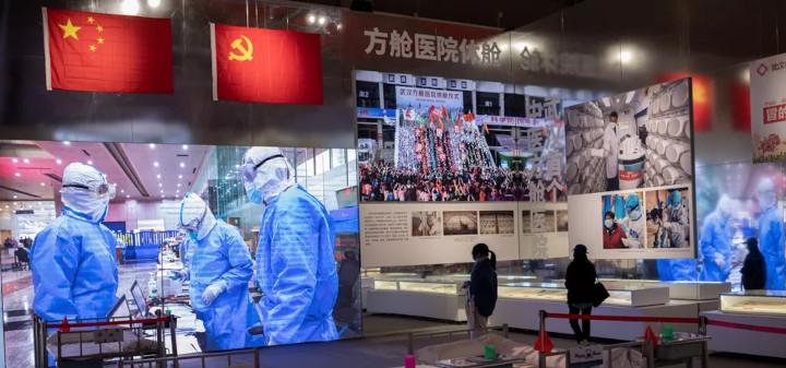 Des visiteurs prennent part à une exposition mettant en scène la gestion de l'épidémie de Covid-19 à Wuhan (Chine), dans l'un des anciens hôpitaux de fortune construits pendant la crise sanitaire, le 15 janvier 2021. © NICOLAS ASFOURI / AFP