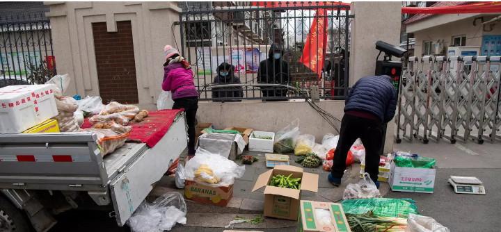 Des vendeurs de légumes devant l'entrée d'un complexe résidentiel qui a été verrouillé suite à l'apparition de nouveaux cas de Covid-19 à Shijiazhuang, dans la province de Hebei, en Chine, le 19 janvier 2021. © REUTERS - STRINGER