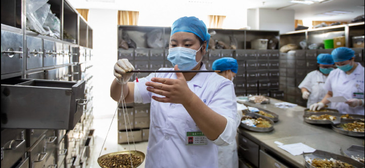 A pharmacist weighs traditional Chinese medicine on scales at a TCM hospital in Haian, Jiangsu province, on May 11, 2020. . © ZHAI HUIYONG/FOR CHINA DAILY