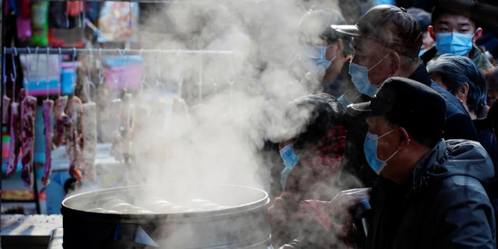 People wearing face masks wait to buy food from a steamed food stall at a street market in Wuhan, Hubei province. Photo: Reuters