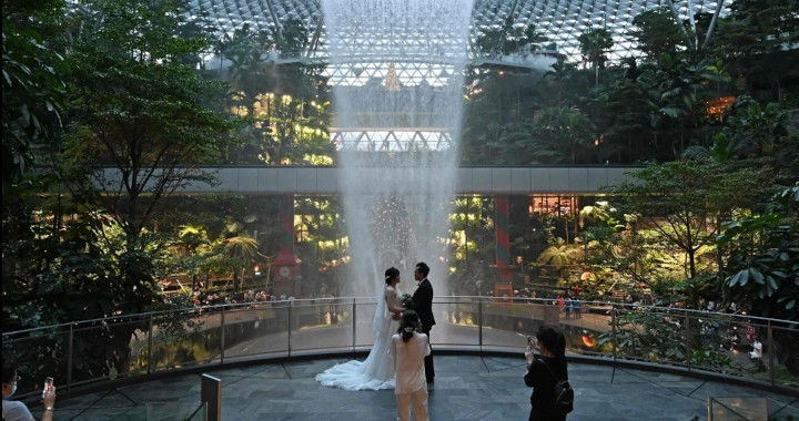 A newly-wedded couple poses for their photographer against the Rain Vortex at Changi Jewel in Singapore in December, 2020. © AFP