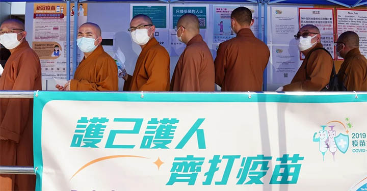 Monks queue for a Covid-19 shot in Tuen Mun on Monday. © Sam Tsang