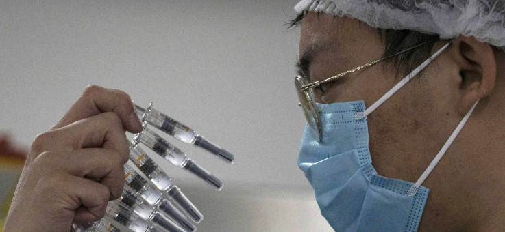 Un employé inspecte les seringues d'un vaccin contre le Covid-19 produit par le laboratoire Sinovac, dans son usine de Pékin, le 24 septembre 2020. © NG HAN GUAN / AP