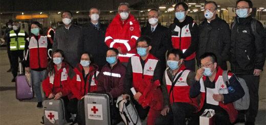 Le 13 mars 2020, des médecins chinois posent pour une photo de groupe après avoir atterri à l'aéroport international Fiumicino de Rome en provenance de Shanghai, apportant plusieurs tonnes d'aide médicale pour combattre l'épidémie deCovid-19 en Italie. © Stringer/ANSA/AFP