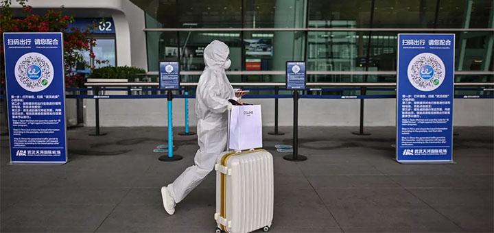 Un passager portant une combinaison de protection et un masque facial passe devant les codes QR de santé de la ville de Wuhan, pour être scanné avant d'entrer dans l'aéroport de Tianhe, dans la province centrale du Hubei en Chine, le 11 avril 2020. © Hector Retamal, AFP