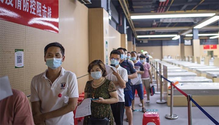 Des gens portant des masques font la queue pour recevoir des vaccins contre la COVID-19 dans un site de vaccination de l'arrondissement de Jiangxia, à Wuhan, dans la province chinoise du Hubei (centre), le 9 juin 2021. @ Xiao Yijiu / Xinhua