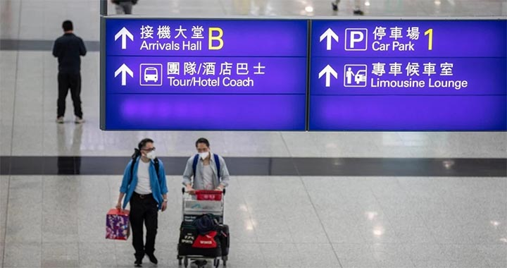 Passengers walk through the arrival hall at Hong Kong International Airport. © EPA-EFE