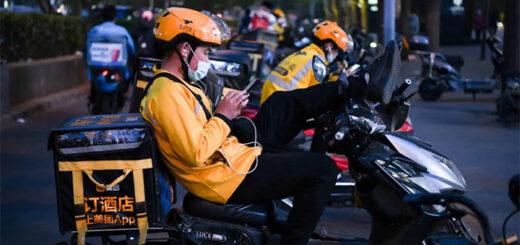 Des livreurs se reposent sur leurs scooters électriques en attendant des commandes à l'extérieur d'un restaurant à Pékin, le 26 avril 2021. © Greg Baker/AFP