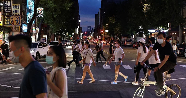 People head towards a newly reopened night market in Taipei on Friday. © Reuters