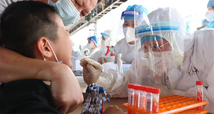 A child is tested for Covid-19 in Xiamen, one of three cities affected by an outbreak of the Delta variant in Fujian province. @ AFP